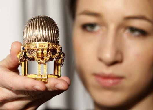 An assistant poses for a photograph with a Faberge egg during a photo-call at  antique dealer Wartski, in central London